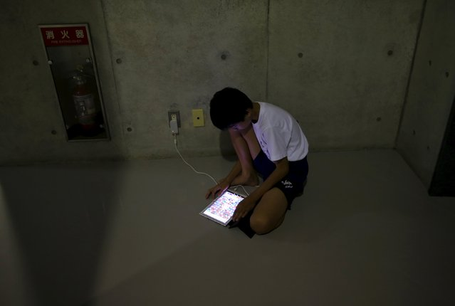An evacuee from an area flooded by the Kinugawa river, caused by typhoon Etau, uses a tablet computer at Ishige Sports Park acting as an evacuation center in Joso, Ibaraki prefecture, Japan, September 10, 2015. (Photo by Issei Kato/Reuters)
