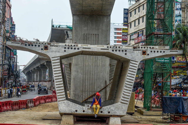 A labourer of the Dhaka Metro Rail project sits on a building material on a street during a government-imposed nationwide lockdown as a preventive measure against the COVID-19 coronavirus, in Dhaka on April 22, 2020. (Photo by Munir Uz Zaman/AFP Photo)