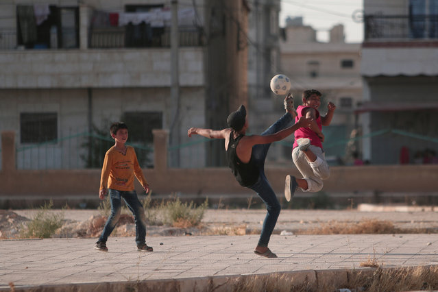 Youths play soccer on a street in Manbij, in Aleppo Governorate, Syria, August 9, 2016. (Photo by Rodi Said/Reuters)
