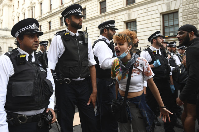 Police officers form a line to block protesters in central London on Wednesday, June 3, 2020 after a demonstration over the death of George Floyd, a black man who died after being restrained by Minneapolis police officers on May 25. Protests have taken place across America and internationally, after a white Minneapolis police officer pressed his knee against Floyd's neck while the handcuffed black man called out that he couldn't breathe. The officer, Derek Chauvin, has been fired and charged with murder. (Photo by Yui Mok/PA Wire via AP Photo)
