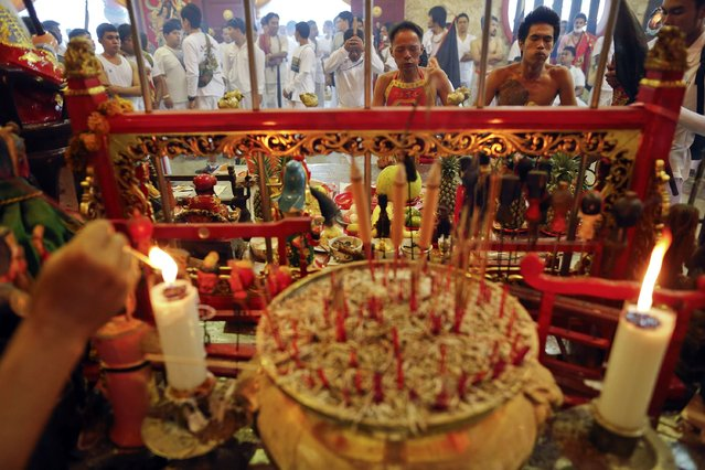 Devotees of the Ban Tha Rua Chinese shrine works themselves into trance before a procession celebrating the annual vegetarian festival in Phuket September 28, 2014. (Photo by Damir Sagolj/Reuters)