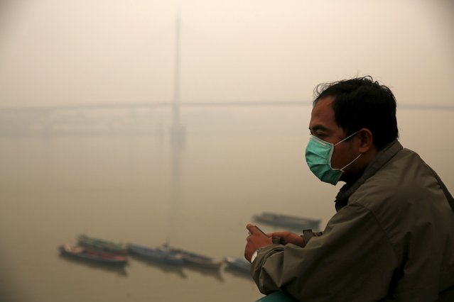 A worker stands as the haze shrouded Batanghari River in Jambi, on Indonesia's Sumatra island, September 15, 2015. (Photo by Reuters/Beawiharta)
