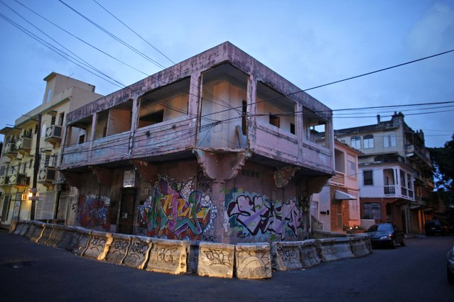 In this September 21, 2014 photo, an abandoned building declared public nuisance sits waiting to be demolished in the Santurce neighborhood in San Juan, Puerto Rico. The area turned to slums in the 1970s as people moved out to suburbs near San Juan. Many who stayed behind were immigrants, mostly from the Dominican Republic and often living in large blocks of public housing dominated by drug gangs amid surging crime in the 1990s. (Photo by Ricardo Arduengo/AP Photo)