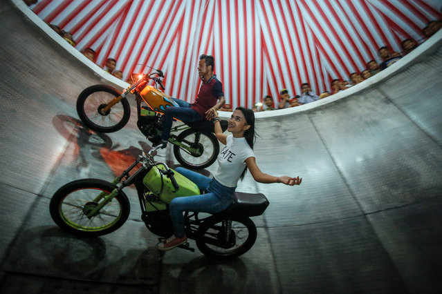 """A picture made available on 16 August 2016 shows a young dare devil motorbike rider, Karmila Purba (Front), 18, riding her motorbike with her colleague inside a barrel locally known as """"Tong Setan"""" or Davil's Barrel, at a traditional night carnival in Deliserdang, North Sumatra, Indonesia, 13 August 2016. (Photo by Dedi Sinuhaji/EPA)"""