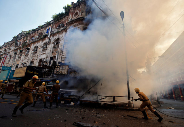 Firefighters try to douse a fire that broke out in a commercial building in a market in Kolkata, India, November 9, 2017. (Photo by Rupak De Chowdhuri/Reuters)