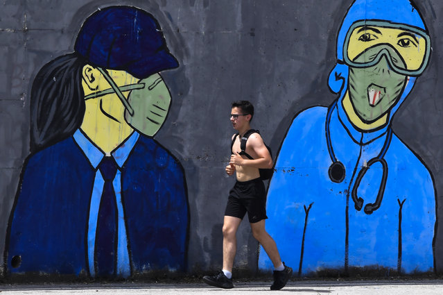 A man runs in front of a mural inspired by the COVID-19 coronavirus pandemic in Skopje, Republic of North Macedonia, 08 June 2020. After an 80-hour curfew, many people left their homes. According to reports, the number of newly infected COVID-19 patients in the North Macedonia is still more than one hundred per day in the last two weeks. The government is considering to continue with preventive measures in the country. (Photo by Georgi Licovski/EPA/EFE)