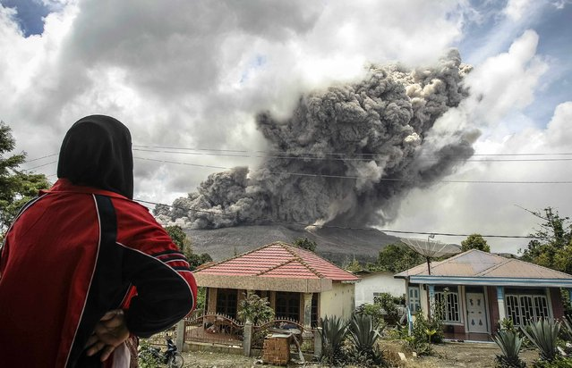 A woman in a village in Karo regency watches Mount Sinabung erupt in Indonesia's North Sumatra province October 8, 2014. The volcano, which has been active since September 2013, erupted in February, killing at least 15 people and forcing thousands to evacuate their homes on the western island of Sumatra. There have been no casualties reported from this latest eruption, which has been happening for the last four days, according to local media. (Photo by Y. T. Haryono/Reuters)