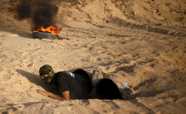 A Palestinian militant from al-Husine brigade loyal to Fatah movement exits from a tunnel during a military-style exercise graduation ceremony in Khan Younis in the southern Gaza Strip, September 20, 2015. (Photo by Suhaib Salem/Reuters)