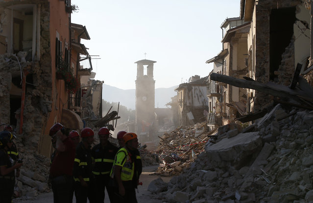 Firefighters work along the main street in Amatrice, central Italy, Saturday, August 27, 2016 where a 6.1 earthquake struck just after 3:30 a.m., Wednesday. As Italians observed a day of national mourning, President Sergio Mattarella and Premier Matteo Renzi joined grieving family members for a state funeral for some of the victims of Wednesday's quake. (Photo by Antonio Calanni/AP Photo)