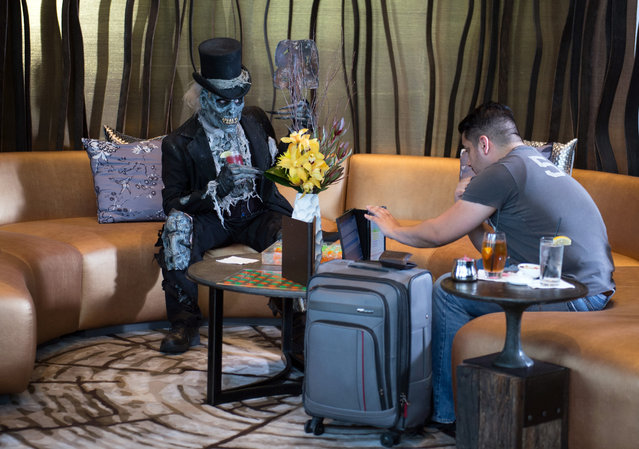The Collector from Netherworld Haunted House with a hotel guest David Gavaldon, of Las Vegas, at Living Room at W Atlanta Downtown hotel on Thursday, October 7, 2014. (Photo by Hyosub Shin/AJC)