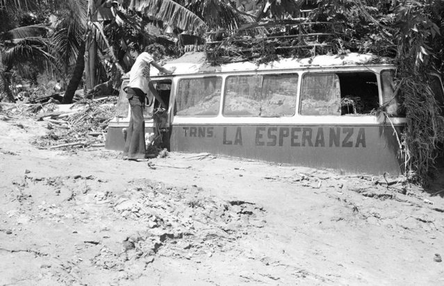An unidentified man tries to clean mud from inside and around a minibus that was half buried when floodwaters from Hurricane Fifi inundated the northwest Honduras town of Choloma, Honduras, September 23, 1974, where almost 3,000 persons are known to have been killed. The words in Spanish on the side of the bus mean Hope Transportation. (Photo by AP Photo)