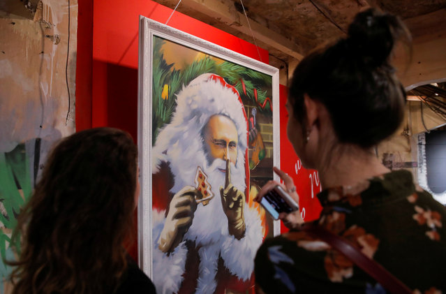 "People look at the paintings depicting Russian president Vladimir Putin dressed as Father Frost, Russian equivalent of Santa Claus, at the ""SUPERPUTIN"" exhibition at UMAM museum in Moscow, Russia on December 6, 2017. (Photo by Maxim Shemetov/Reuters)"