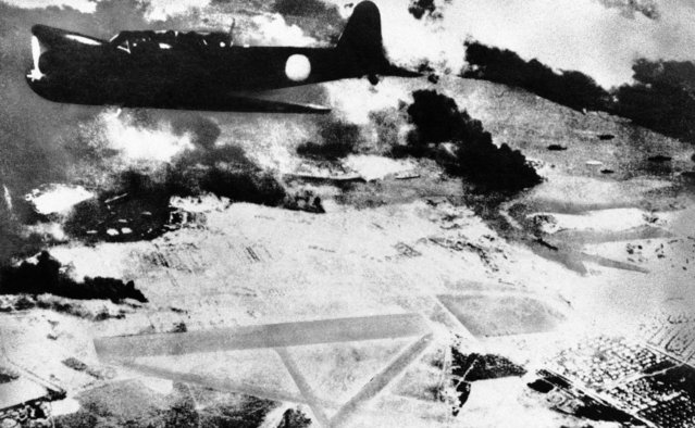 A Japanese bomber on a run over Pearl Harbor, Hawaii is shown during the surprise attack of December 7, 1941. Black smoke rises from American ships in the harbor. Below is a U.S. Army air field. (Photo by Associated Press)