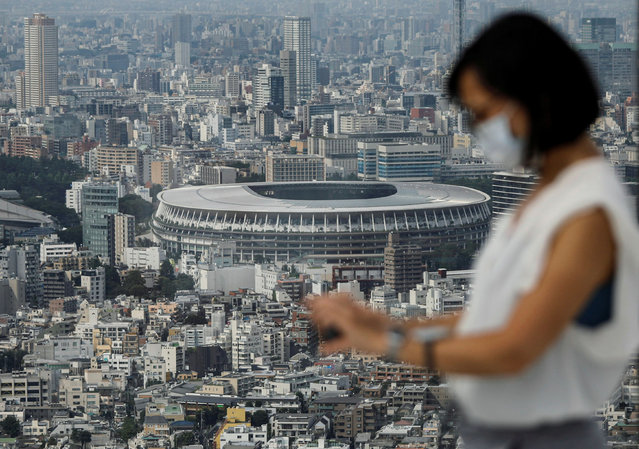 The National Stadium, the main stadium of Tokyo 2020 Olympics and Paralympics, is seen through a visitor wearing a protective face mask amid the coronavirus disease (COVID-19) at an observation deck in Tokyo, Japan on July 20, 2020. (Photo by Issei Kato/Reuters)