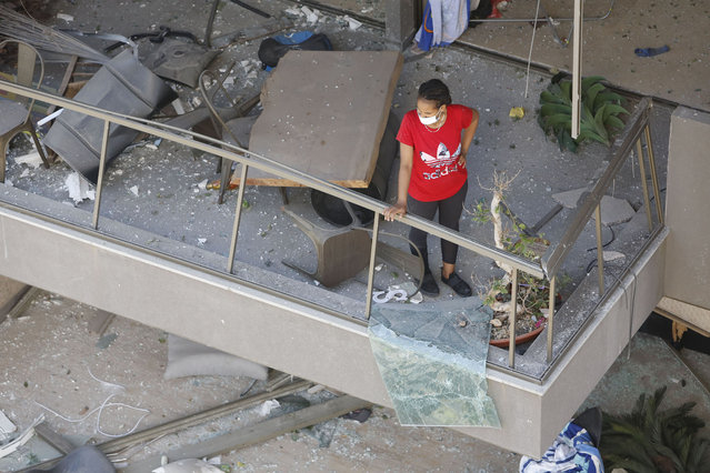 A woman looks down from a balcony, damaged by an explosion a day earlier, on August 5, 2020 in Beirut, Lebanon. As of Wednesday morning, more than 100 people were confirmed dead, with thousands injured, when an explosion rocked the Lebanese capital. Officials said a waterfront warehouse storing explosive materials, reportedly 2,700 tons of ammonium nitrate, was the cause of the blast. (Photo by Marwan Tahtah/Getty Images)