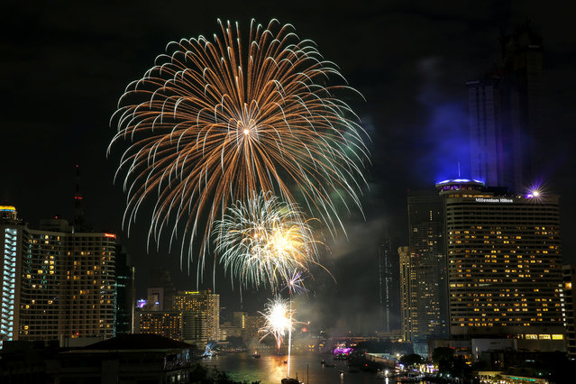 Fireworks explode over Chao Phraya River during New Year's celebrations in Bangkok, Thailand January 1, 2018. (Photo by Athit Perawongmetha/Reuters)