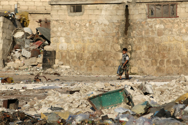 A boy walks past garbage and debris in the rebel-held al-Sheikh Said neighbourhood of Aleppo, Syria September 1, 2016. (Photo by Abdalrhman Ismail/Reuters)