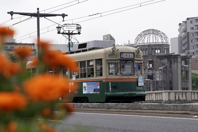A running tram is seen near the Atomic Bomb Dome in Hiroshima, western Japan, Monday, August 3, 2020. A tram which survived the Hiroshima atomic bombing will run, without any passenger, on the streets on Aug. 6 to commemorate the day of atomic bombing in the city. (Photo by Eugene Hoshiko/AP Photo)