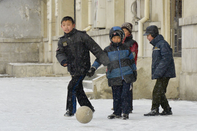 Young boys play football on the streets of the capital in February 2013, in Pyongyang, North Korea. (Photo by Andrew Macleod/Barcroft Media)