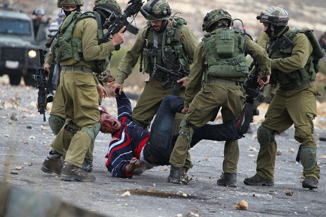Israeli soldiers detain a wounded Palestinian stone thrower after infiltrated members of the Israeli security forces shot at fellow protesters during clashes in Beit El, on the outskirts of the West Bank city of Ramallah, on October 7, 2015. New violence rocked Israel and the Israeli-occupied West Bank, including a stabbing in annexed east Jerusalem, even as Israel and Palestinian president Mahmud Abbas took steps to ease tensions. (Photo by Abbas Momani/AFP Photo)
