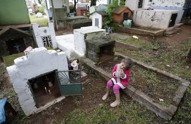 A girl sits near the grave of a relative at a cemetery during the observance of All Souls' Day in Asuncion, Paraguay, on November 2, 2014. (Photo by Jorge Adorno/Reuters)