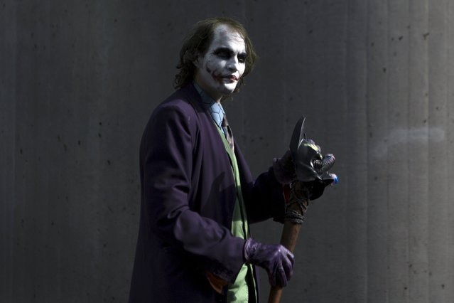 "A man dressed as The Joker from ""Batman"" walks around the exterior on day two of New York Comic Con in Manhattan, New York, October 9, 2015. (Photo by Andrew Kelly/Reuters)"