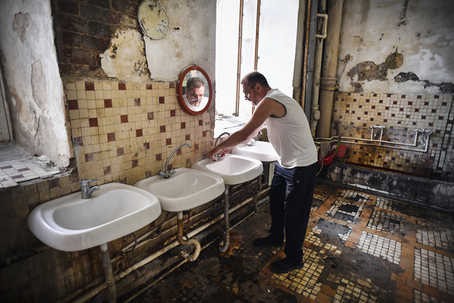 Vladimir Mogilnikov, 62, washes his hands in a communal washing room in a dormitory for the workers of Proletarka textile factory in the town of Tver, 200 kilometres north-west from Moscow on August 8, 2020. (Photo by Andrey Borodulin/AFP Photo)