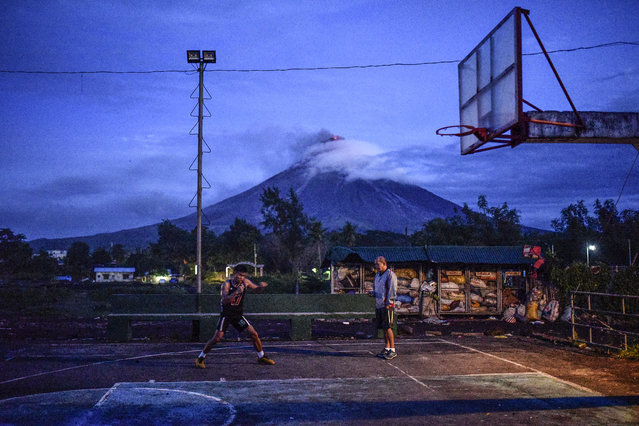 A resident practices boxing at a basketball court in Daraga, Albay province, Philippines, January 25, 2018. (Photo by Ezra Acayan/NurPhoto via Getty Images)