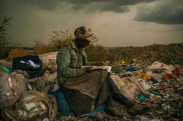 """This picture by US photographer Micah Albert, freelance documentary photographer represented by Redux Pictures photo agency is the 1st Prize Contemporary Issues Single in the 56th World Press Photo Contest, it was announced by the organizers on 15 February 2013 in Amsterdam, The Netherlands. Pausing in the rain, a woman working as a trash picker at the 30-acre dump, which literally spills into households of one million people living in nearby slums, wishes she had more time to look at the books she comes across. She even likes the industrial parts catalogs. """"It gives me something else to do in the day besides picking trash"""", she said. This is picture is dated 03 April 2012 in Nairobi, Kenya. (Photo by Micah Albert/EPA)"""