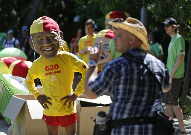 A protester, is seen wearing a mask depicting U.S. President Barack Obama, and an Australian life guard outfit during a demonstration calling for global equality among nations outside the site of the venue of the annual G20 leaders summit in Brisbane, November 14, 2014. Leaders of the top 20 industrialized nations will gather in Brisbane November 15-16 for their annual G20 summit. (Photo by Jason Reed/Reuters)