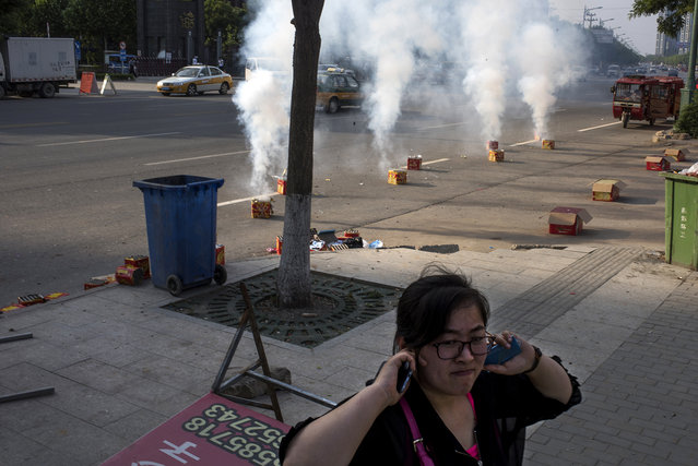 A woman plugs her ears as firecrackers go off in the streets of Yanjiao, a rapidly expanding satellite city of over 700,000 people, outside Beijing, on May 21, 2016. (Photo by Michael Robinson Chavez/The Washington Post)