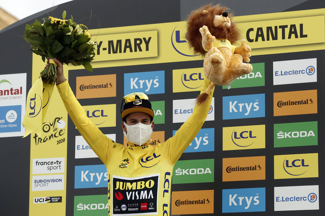 Slovenia's Primoz Roglic wearing the overall leader's yellow jersey celebrates in the podium after the stage 13 of the Tour de France cycling race over 191 kilometers from Chatel-Guyon to Puy Mary, Friday, September 11, 2020. (Photo by Benoit Tessier/Pool via AP Photo)