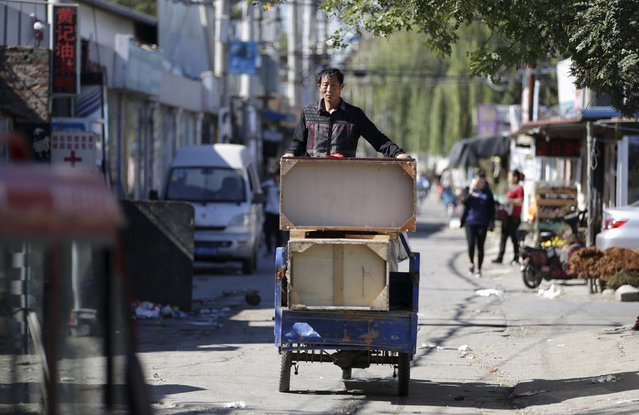 A man stands on the back of a tricycle as he travels inside a residential area for migrant workers on the outskirts of Beijing, China, October 13, 2015. (Photo by Jason Lee/Reuters)