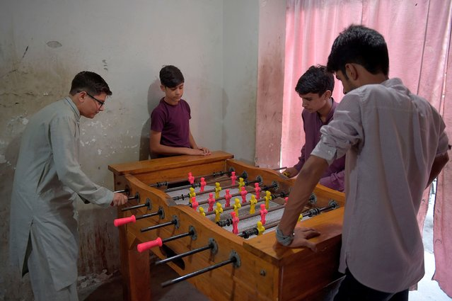 Youths play table football at a shop in Rawalpindi on September 7, 2020, while the government announced reopening education institutes starting from September 15, nearly six months after the Covid-19 coronavirus pandemic sent students home. (Photo by Farooq Naeem/AFP Photo)