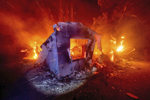 Flames from the LNU Lightning Complex fires consume a home in unincorporated Napa County, Calif., on Wednesday, August 19, 2020. Fire crews across the region scrambled to contain dozens of wildfires sparked by lightning strikes. (Photo by Noah Berger/AP Photo)