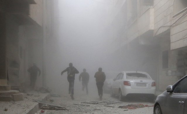 People run amid smoke from a site hit by what activists said were air strikes by forces loyal to Syria's President Bashar al-Assad in Raqqa, eastern Syria, which is controlled by the Islamic State November 27, 2014. (Photo by Nour Fourat/Reuters)