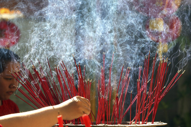 A woman places incense sticks during celebrations of the Lunar New Year at a temple in Bali, Indonesia, Friday, February 16, 2018. (Photo by Firdia Lisnawati/AP Photo)
