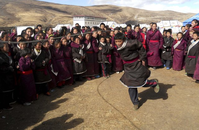 Tibetan students from a local primary school skip rope as they exercise near their temporary tents after an earthquake hit Kangding county, Sichuan province November 23, 2014. At least four people were killed and 54 others injured on Saturday after a 6.3 magnitude quake hit Kangding County in southwest China's Sichuan Province, Xinhua News Agency reported. (Photo by Reuters/China Daily)