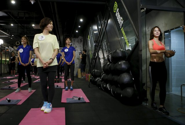 "Ray Yang (R), a celebrity trainer, arrives during TV program ""The Body Show"" at a gym in Seoul, September 19, 2015. (Photo by Kim Hong-Ji/Reuters)"