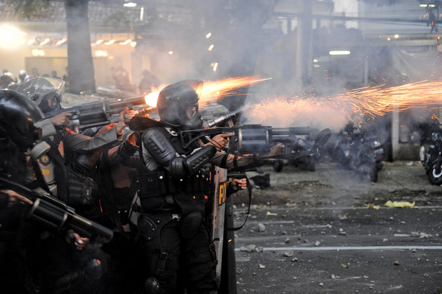 Police officers fire their tear gas launchers during a clash with student protesters in Bandung, West Java, Indonesia, Wednesday, October 7, 2020. Thousands of Indonesian students and workers protested on Wednesday against a new law they say will cripple labor rights and harm the environment, with some clashing with police. (Photo by Kusumadireza/AP Photo)