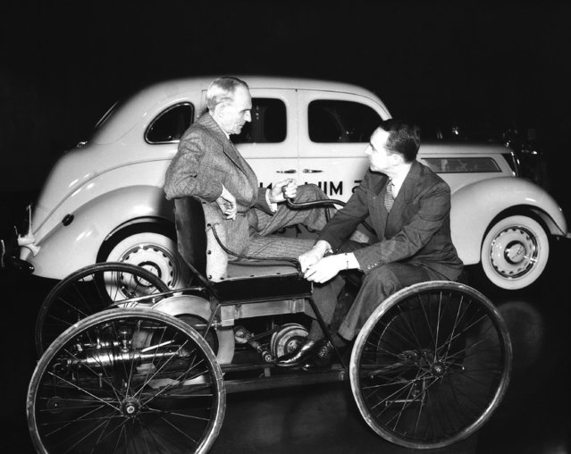 The companionship that exists between the rulers of a mighty automobile manufacture empire Henry Ford and his son, Edsel Ford. Here they are sitting on the elder Ford's first car with the 25-millionth in the background on December 21, 1939. Note the profile resemblance the philosophy of the younger Ford, President of the entirely-family-owned two-billion-dollar concern, is of major importance to the financial and automotive worlds for it will someday determine the fiscal and industrial policies of a huge and vital segment of the world's economic and business structure. (Photo by AP Photo)