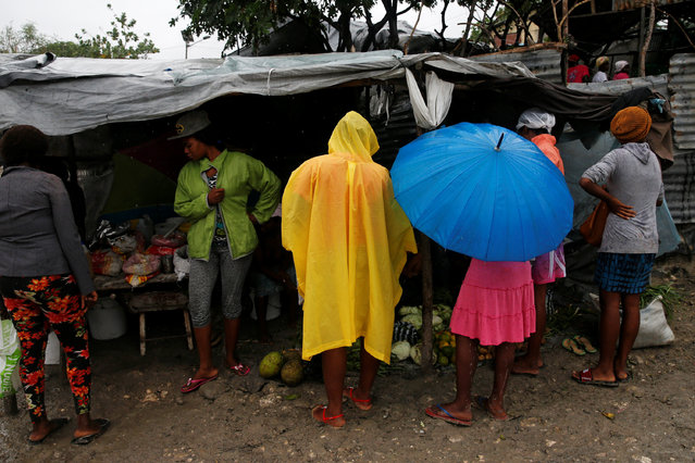 People buy goods on a street at a camp for displaced people while Hurricane Matthew approaches Port-au-Prince, Haiti, October 3, 2016. (Photo by Carlos Garcia Rawlins/Reuters)