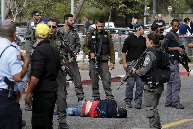 A Palestinian suspected of committing a stabbing attack is surrounded by Israeli border police at the scene of the attack in Jerusalem October 30, 2015. Knife-wielding Palestinians attacked Israelis in Jerusalem and the Israeli-occupied West Bank and one of assailants was shot dead, police said. (Photo by Ammar Awad/Reuters)