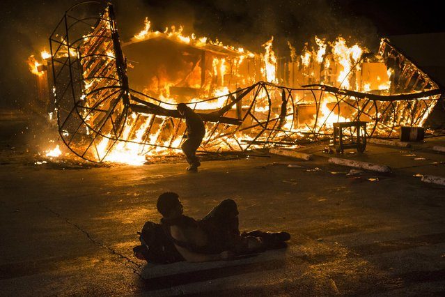 A resident, lying shirtless, keeps warm as another approaches the blazing skeleton of Juanita's Fashions R Boutique after it was burned to the ground in Ferguson, Missouri early morning November 25, 2014. Gunshots rang out and buildings burned in a Midwestern suburb after a grand jury decided on Monday not to indict a white police officer over the fatal August shooting of an unarmed black teenager, sparking a fresh wave of racially tinged violence. (Photo by Adrees Latif/Reuters)