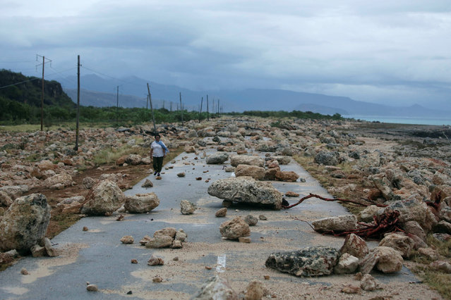 A woman walks on a highway blocked by rocks after the passage of hurricane Matthew on the coast of Guantanamo province, Cuba, October 5, 2016. (Photo by Alexandre Meneghini/Reuters)