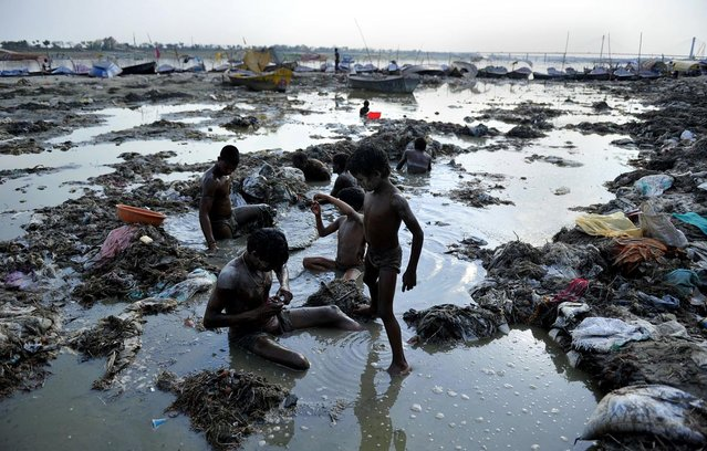 Indian men search for coins and gold in the polluted waters of the Ganga river at Sangam after the Kumbh Mela festival, in Allahabad on April 2, 2013. The two month long Kumbh Mela, celebrated every 12 years at the conjunction of two sacred rivers on the outskirts of the northern Indian city of Allahabad, drew massive crowds of devotees, ascetics and foreign tourists till its conclusion on March 10. (Photo by Sanjay Kanojia/AFP Photo)