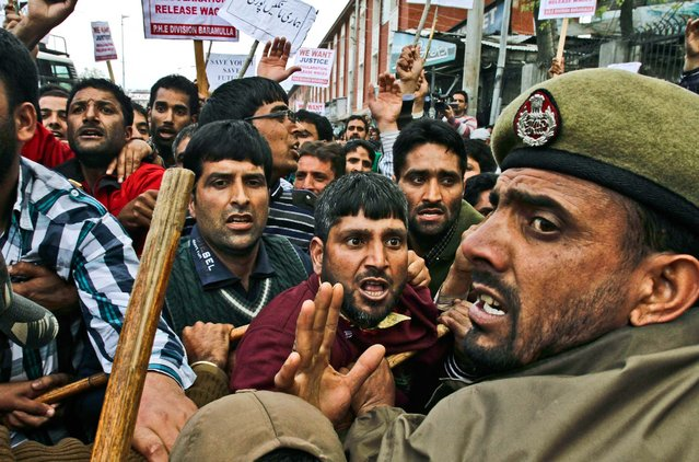 Kashmiri government employees scuffle with police during a protest in Srinagar, India, on April 10, 2013. The government employees were demanding regularization of contractual jobs and a hike in salary. (Photo by Mukhtar Khan/Associated Press)