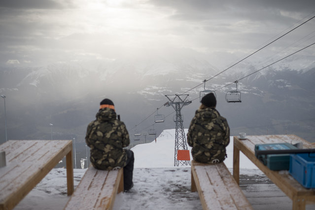 Winter sport enthusiasts take a break on the Crap Sogn Gion overlooking the green valley, in Flims, Switzerland, December 15, 2014. While some mountain railways are open in higher regions of Switzerland, there is hardly any snow in the valley. (Photo by Gian Ehrenzeller/EPA)