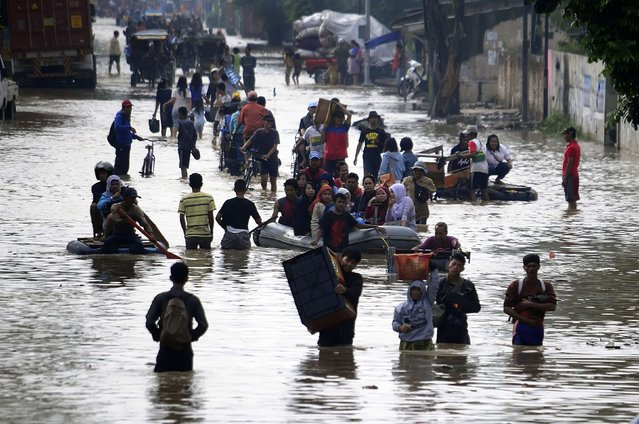 People walk through a flooded street after heavy rain hit an industrial estate area in Bandung regency, in this December 22, 2014 picture taken by Antara Foto. (Photo by Novrian Arbi/Reuters/Antara Foto)