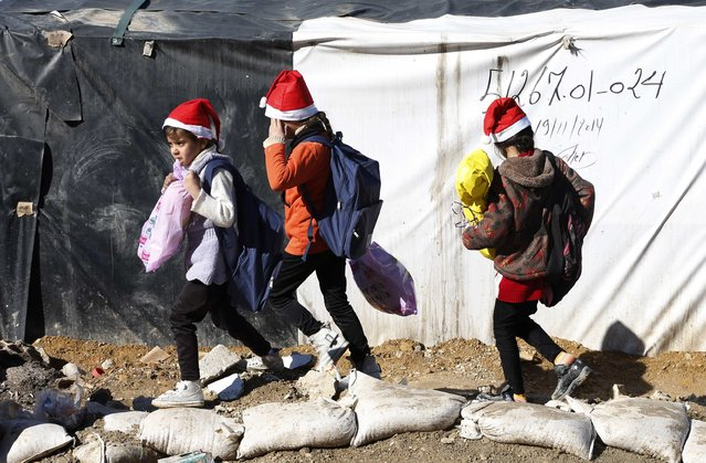 Syrian refugee girls hold their Christmas gifts from SAWA, a non-governmental organisation, in Bar-Elias in the Bekaa valley December 24, 2014. (Photo by Jamal Saidi/Reuters)